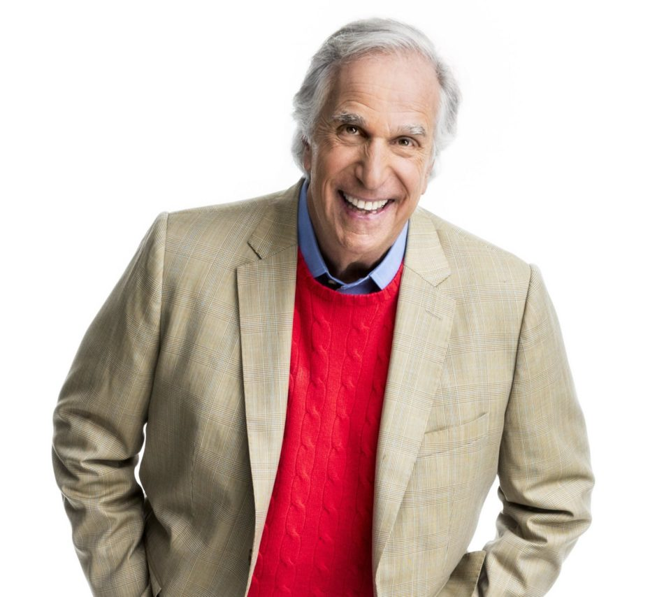 Henry Winkler smiles with his hands in his jacket pocket