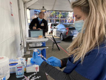 woman prepares vaccination at drive-through vaccination site