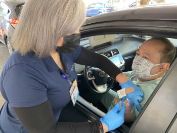 man inside car gets vaccination