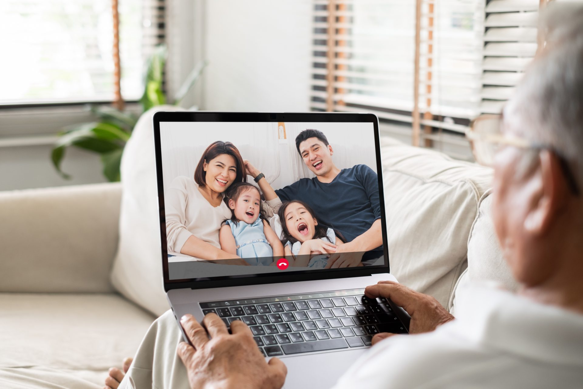 man sits with laptop on his lap talking to family
