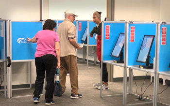 two people near ballot marking devices