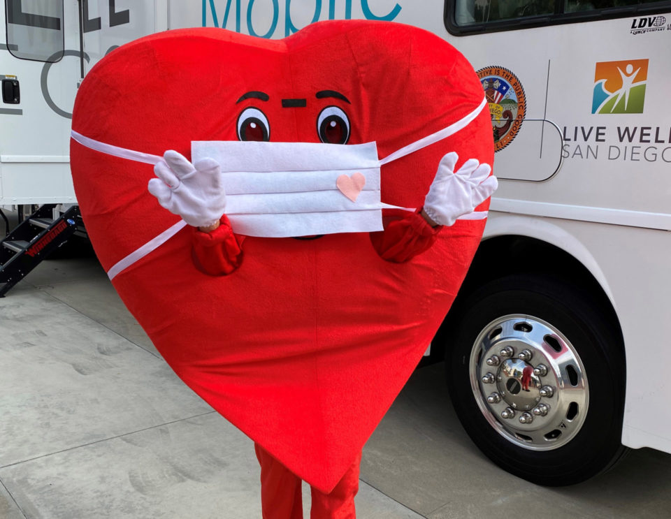 A heart-shaped mascot wearing face mask