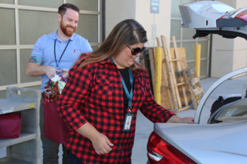 Andrew Deeley, left, and Melissa Hubbard, from the County's Public Administrator/Public Guardian's office, load up their vehicle with donated gifts for vulnerable and at-risk adults.