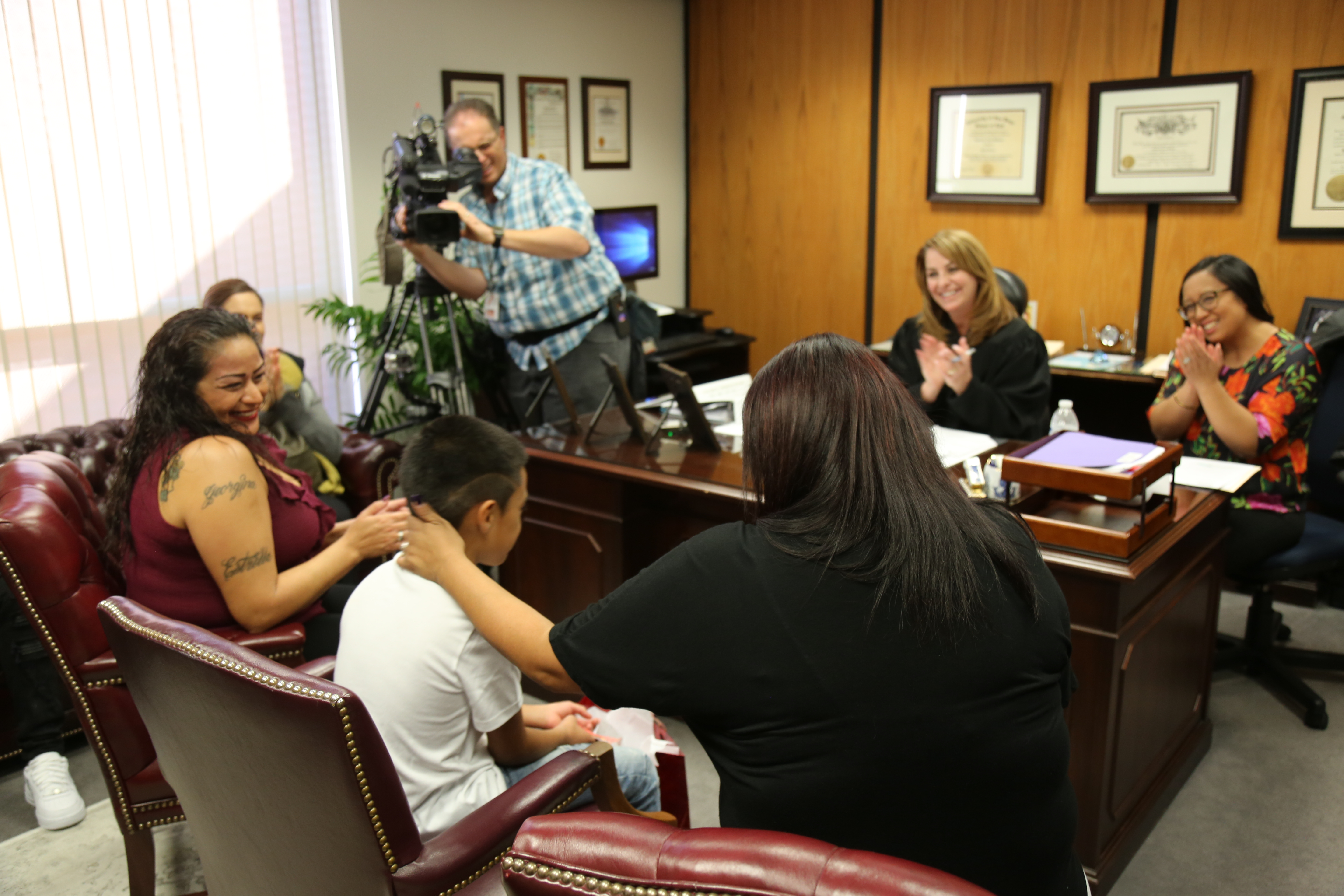Family members,  Superior Court Judge Kimberlee Lagotta and court staff all applaud after the adoption of Hector, by his mother Issis Aranda (right, black shirt), became official.