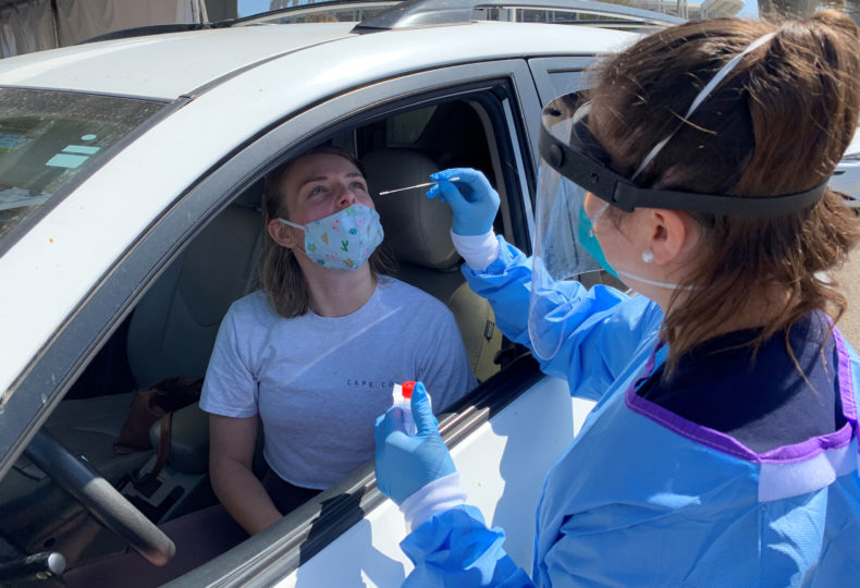 a young woman is being tested for coronavirus while inside her car