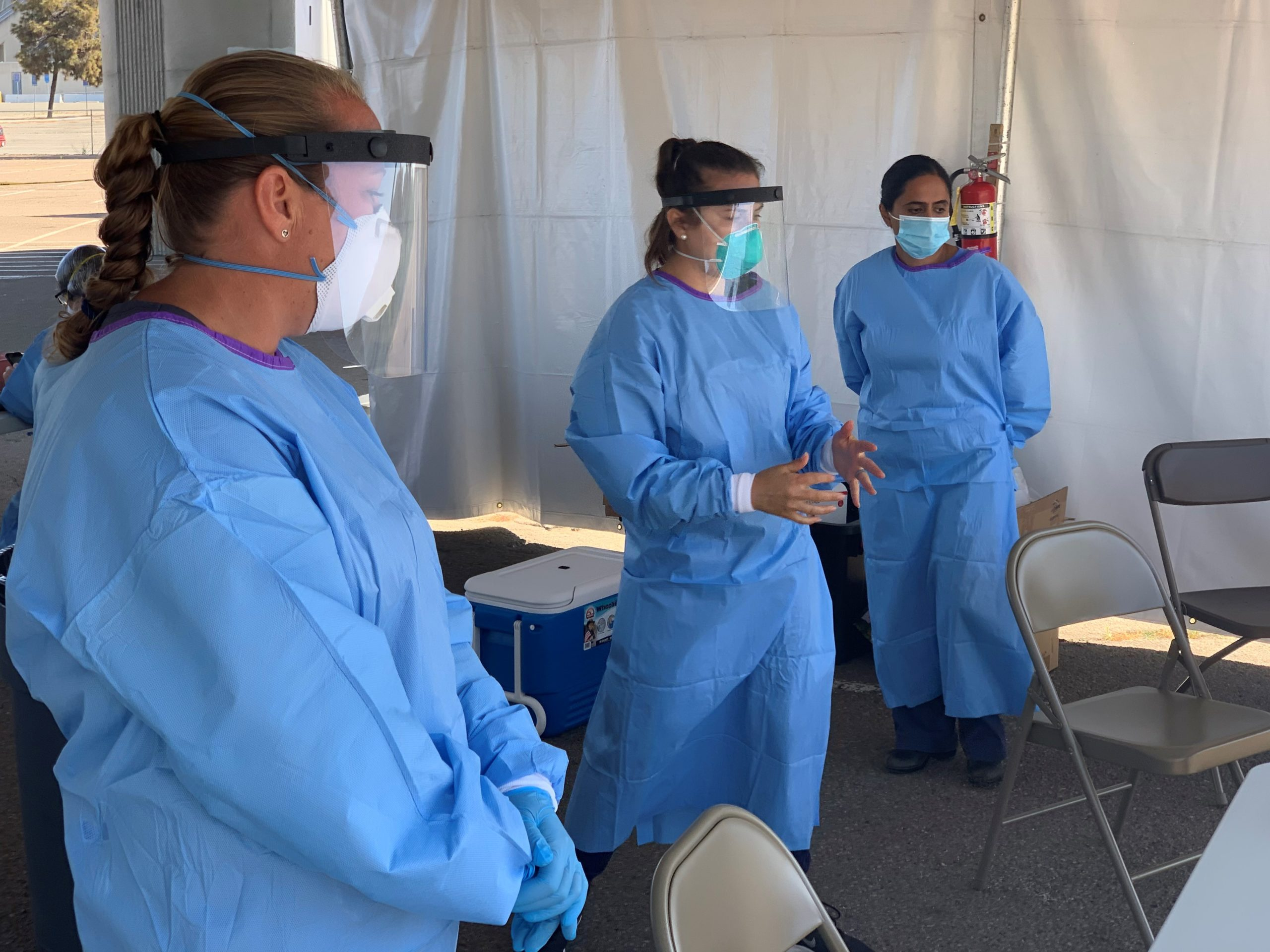 three people wearing protective gowns and masks