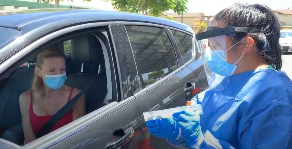 woman in car waits to get a coronavirus test
