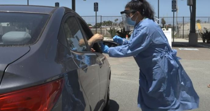 a nurse assisting someone inside a car at a testing facility