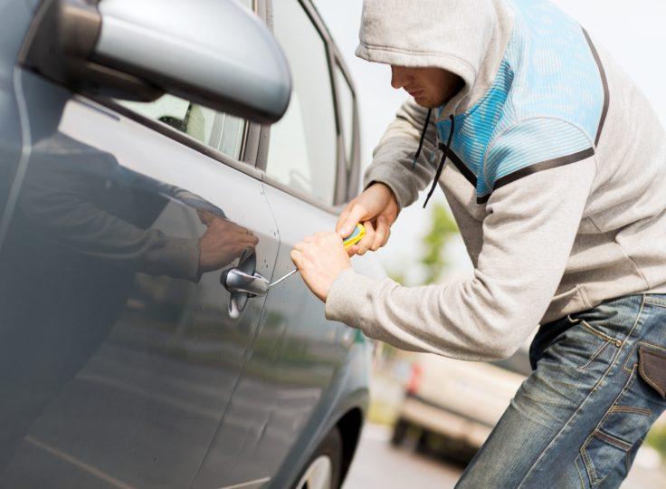 A thief breaks into a car.