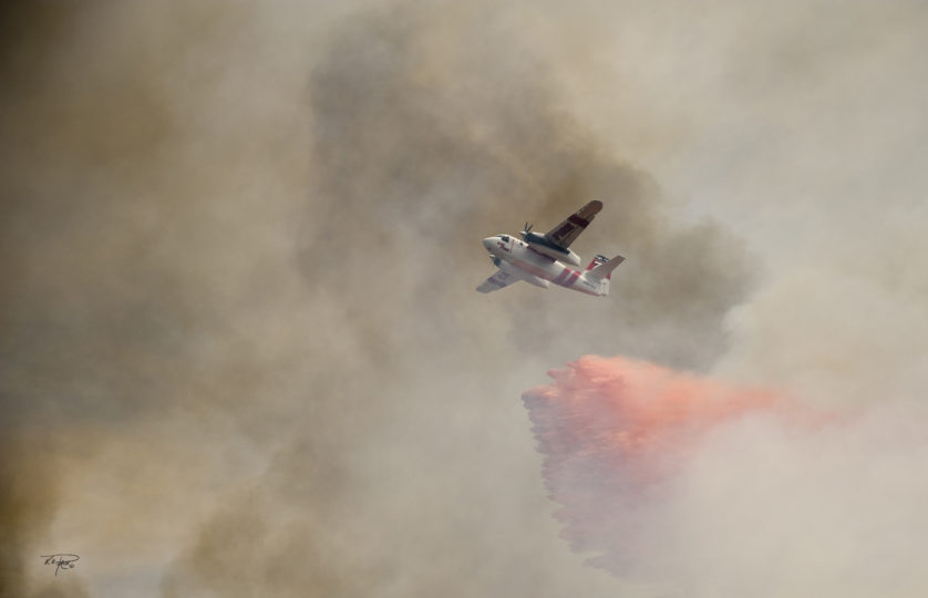 A CAL FIRE air tanker drops retardant on a fire in San Diego County.