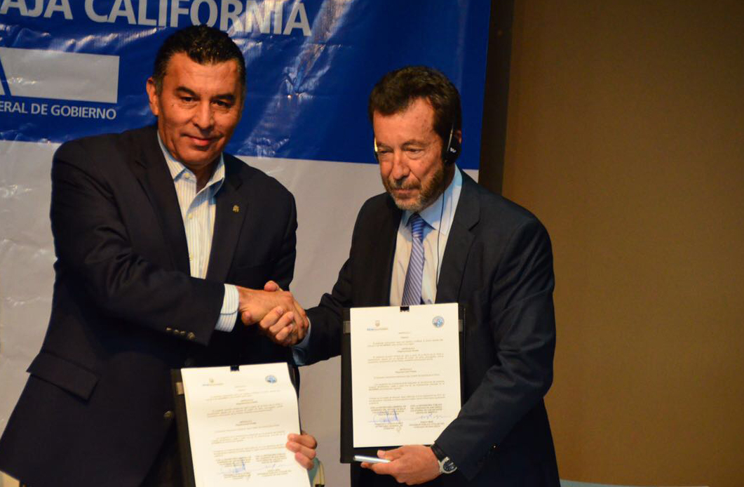 San Diego County Public Defender Randy Mize,  at right, listens in as Lt. Gov. Francisco Rueda Gomez of the State of Baja California shakes his hand at a ceremonial signing of a binational legal agreement on Sept. 8 in Tijuana.