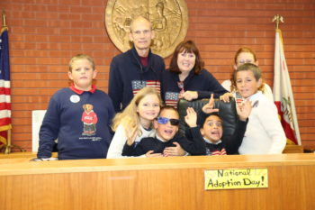 Getting all the kids to sit still for a family photo can be a challenge for the Bonadeo family. After adopting a set of four siblings (Peter, Katherine, David and Dorothea), John Bonadeo and Betty McDonald finalized the adoption of brothers Johnny, center, with sunglasses and James, to his left, during the Court Adoption Party.