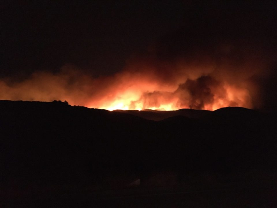 Photo of fire flames on a ridge at night.