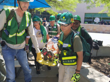 CERT members use a backboard to carry a mock victim to a triage station during a training exercise.