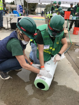 Two CERT members apply direct pressure to a pipe which was squirting water to simulate a bleeding injury.