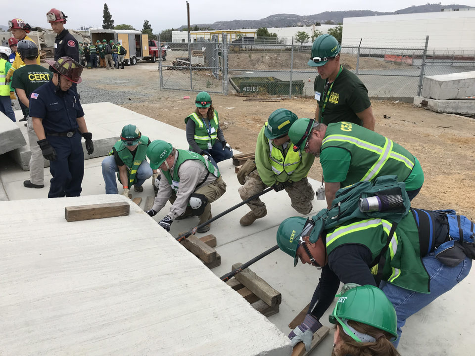 "At a recent Countywide CERT training, members from various communities work together to lift a heavy concrete slab to rescue a ""dummy"" who is trapped just out of sight."