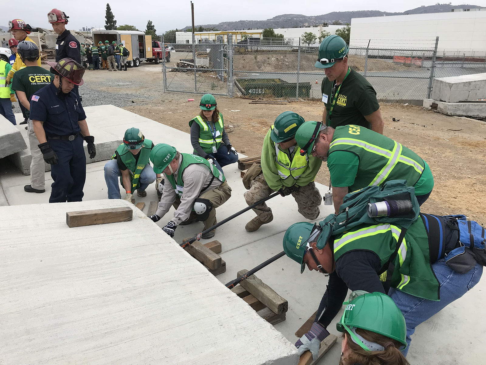 """At a recent Countywide CERT training, members from various communities work together to lift a heavy concrete slab to rescue a """"dummy"""" who is trapped just out of sight."""