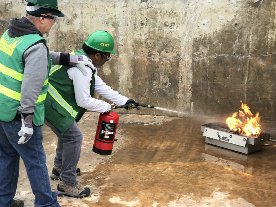 A team member practices using a fire extinguisher to put out a small fire.