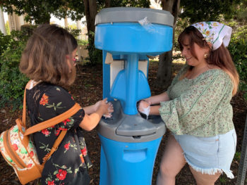 two people using a handwashing station