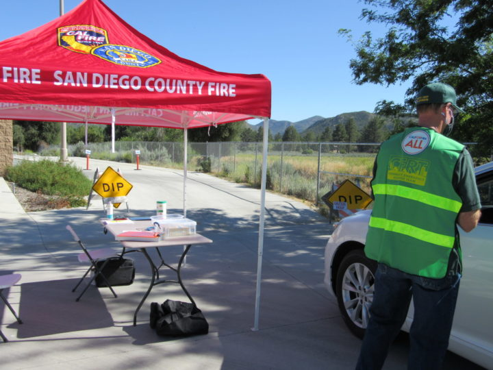 Photo showing a CERT volunteer helping county residents during COVID testing in Pine Valley.
