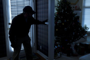 Burglar creeping around a home with a decorated Christmas tree.