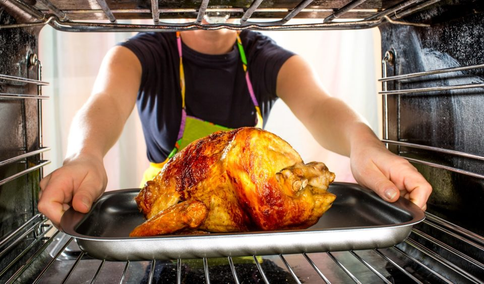 a woman places a turkey into the oven