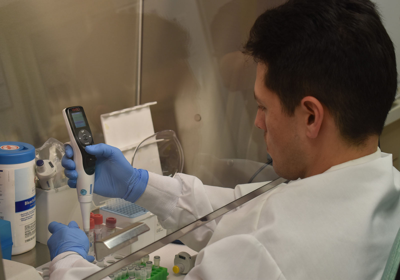 Photo of a lab technican testing a COVID-19 sample