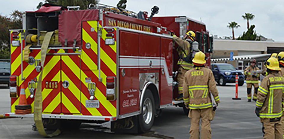 Picture of several County fire trucks and firefighters,