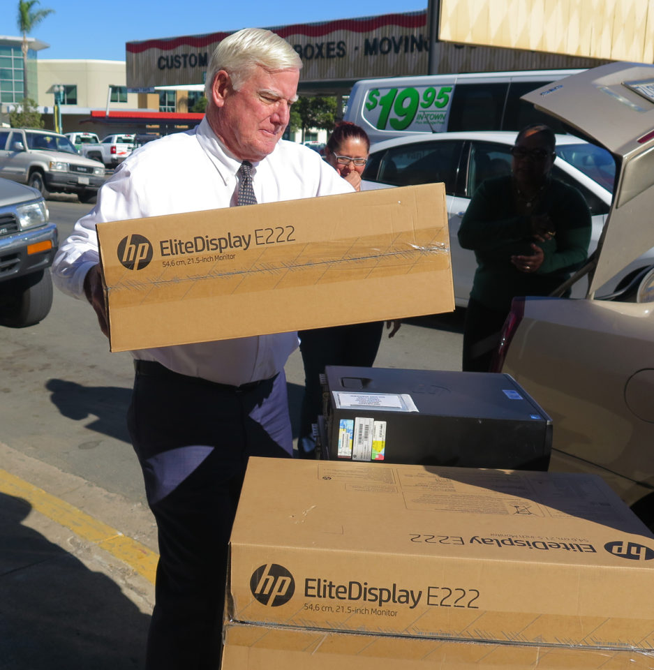 Supervisor Greg Cox delivers computers for foster kids.