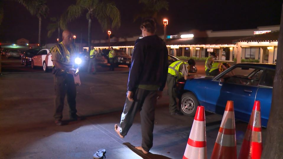 A Sheriff's deputy administers a field sobriety test to a driver at a checkpoint.