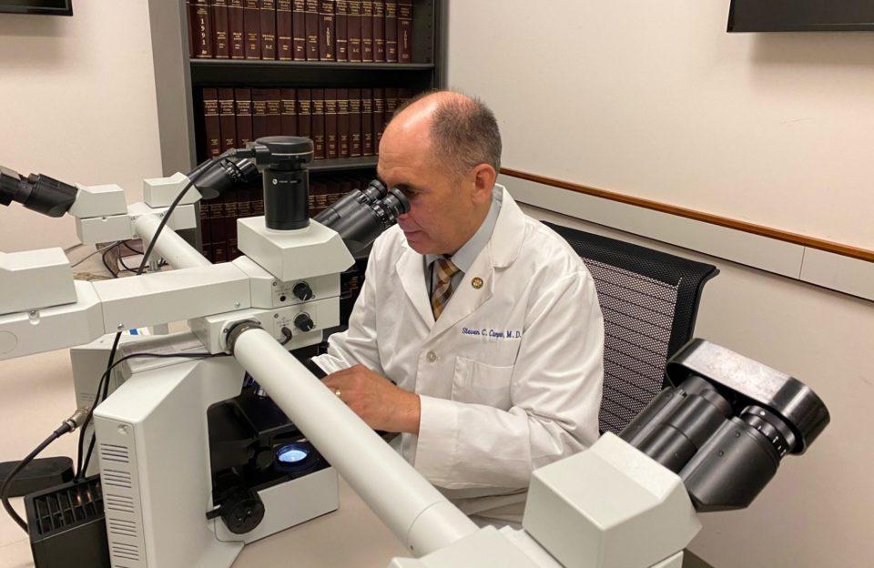 Forensic investigator looks in microscope.