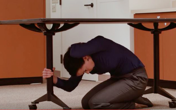 Woman under a table, holding a table leg, covering head.