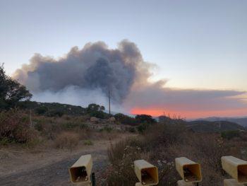 Smoke plume rising and orange glow from fire on ridge