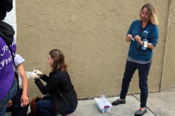 Public Health Nurse Heidi Unruh, right, opens up a band aid while Mindy Coughlin finishes up a vaccination.