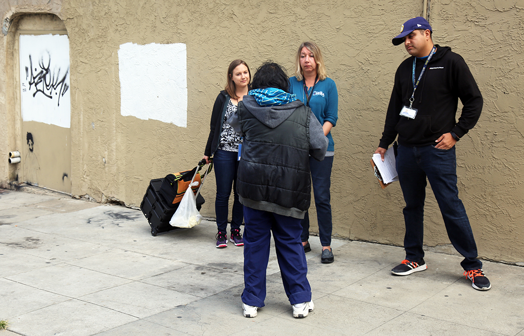 Mindy Coughlin, left, and Heidi Unruh, center, both San Diego County Health and Human Services Agency Public Health Nurses and an outreach worker from Friend to Friend talk to a homeless person about getting the hepatitis A vaccination in downtown San Diego earlier this year.