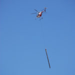A helicopter flies a new utility pole to replace one of the many lost.