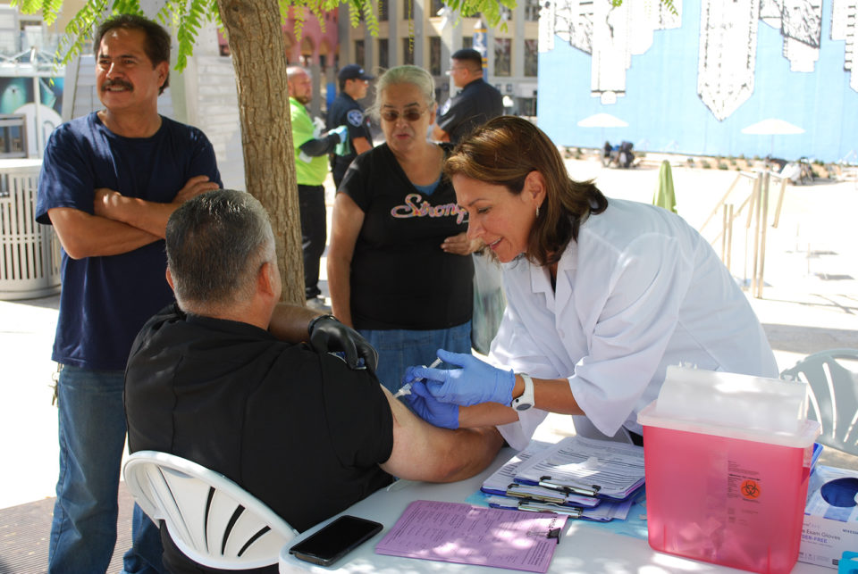 County nurse Paulina Bobenrieth vaccinates a patient in downtown San Diego.