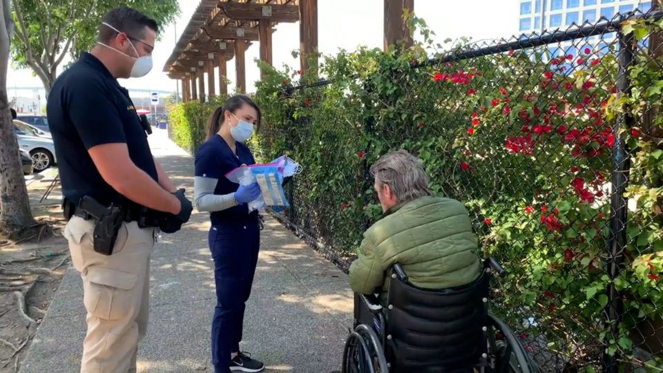 two people talk to a man in a wheelchair