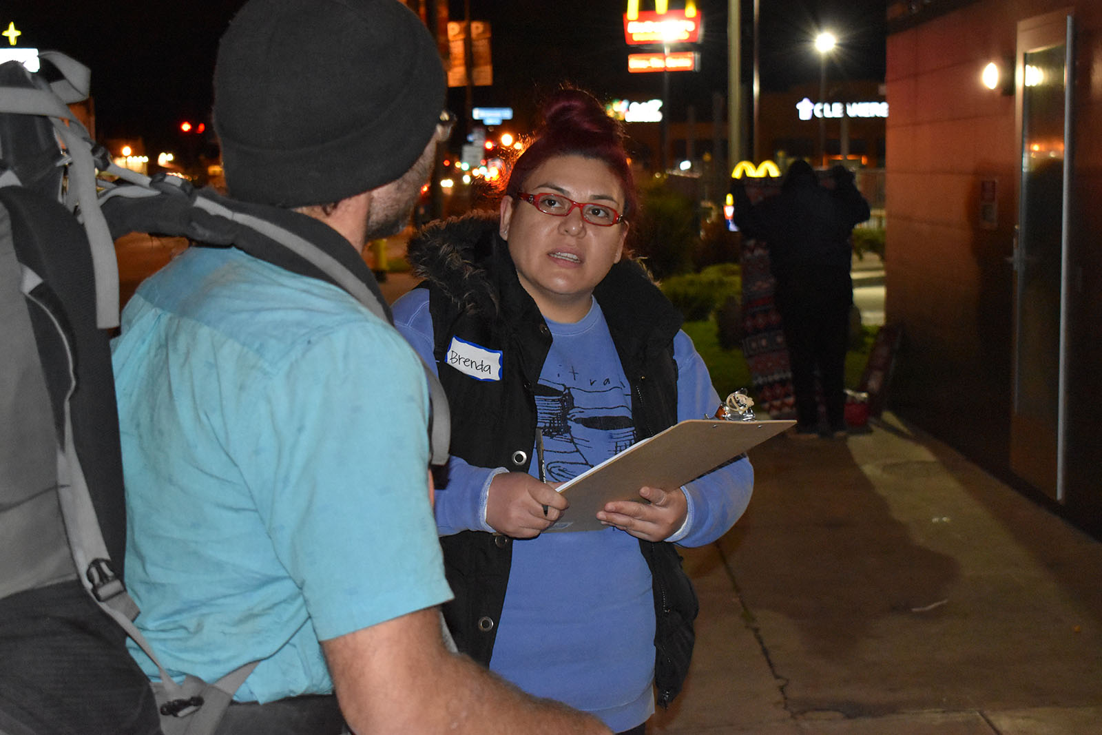 Brenda Velasco, a human services specialist with the County Northeast Family Resource Center, talks to a homeless man on University Ave. in Hillcrest.