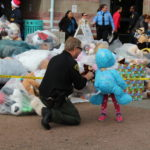 A probation deputy gives a bear to a little girl.