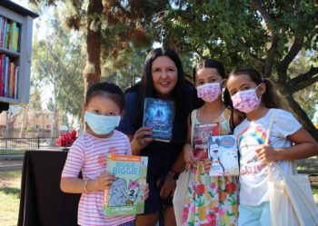 Nora Varas with three girls in front of a Little Free Library