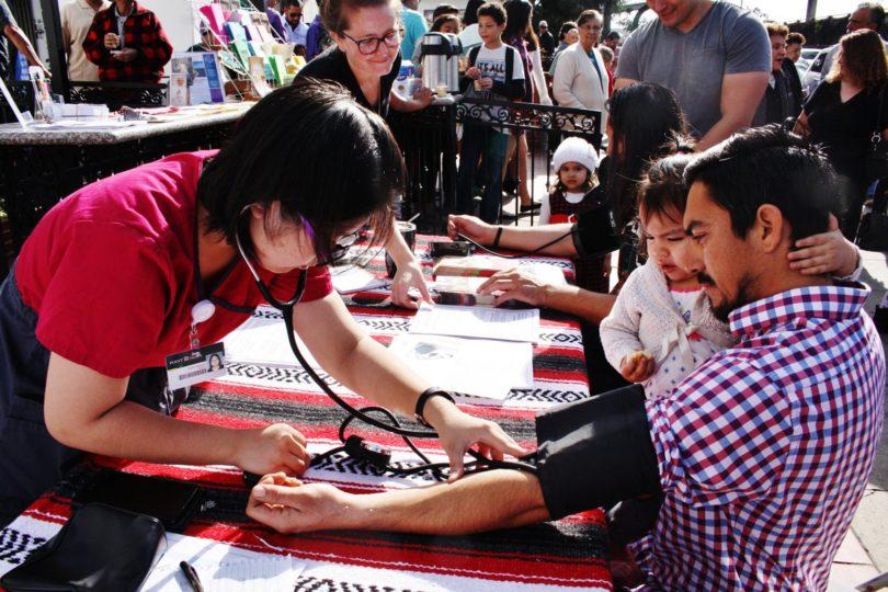 Man getting his blood pressure taken by a woman.