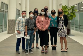 A group of people with masks on stand inside a building