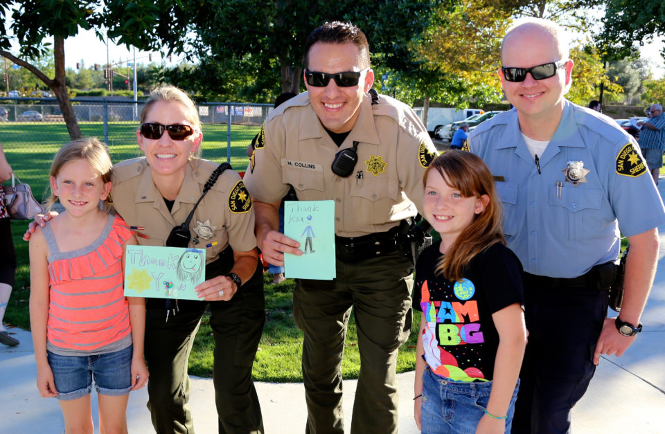 Sheriff's deputies pose with two girls who made them thank you cards.