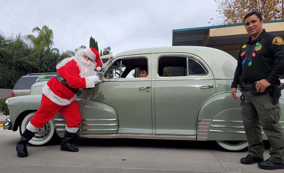 Santa poses with a vintage car and a probation officer.