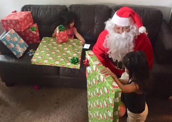 Two young girls receive presents from Santa.