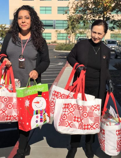 Two women holding several gift bags