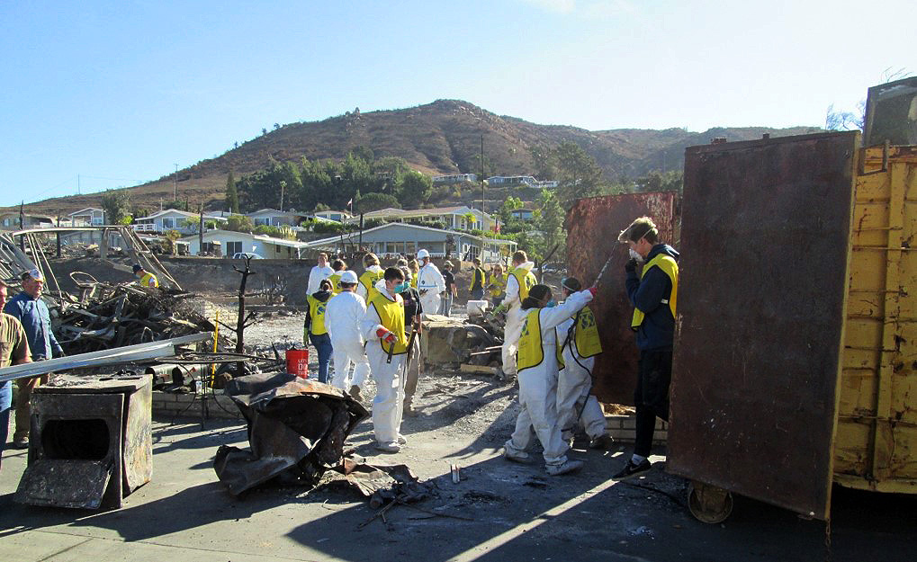 Volunteers remove ash and debris from homes burned in the Lilac Fire.