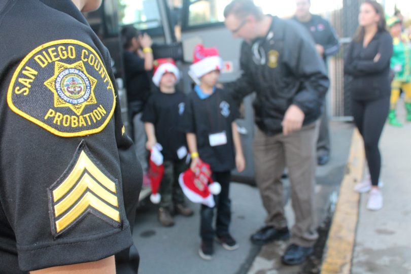 Probation officers assist two children off a bus