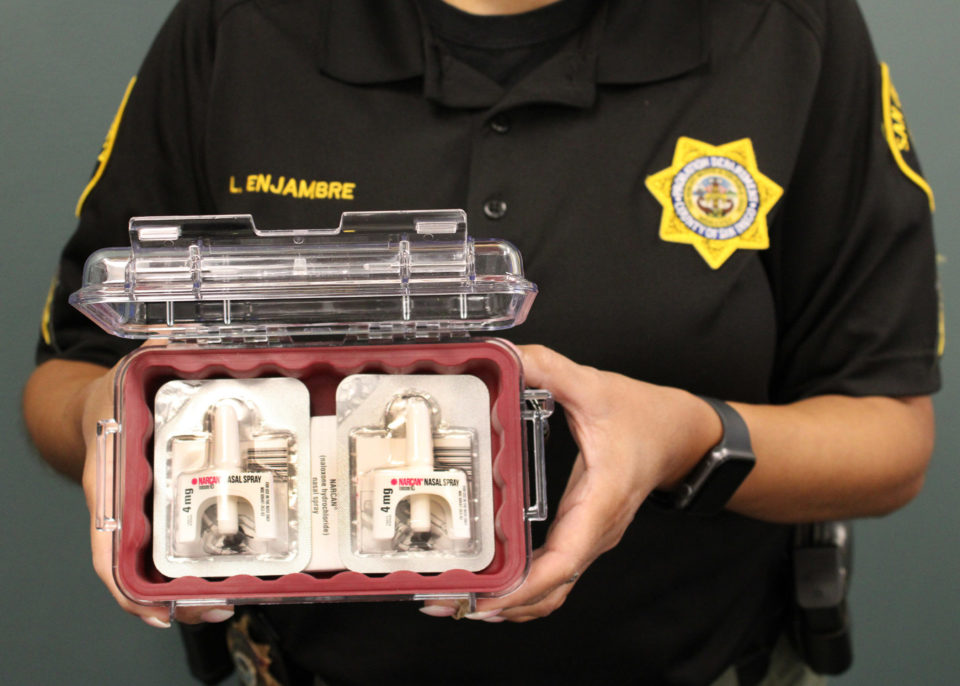 Photo of Probation officer holding the naloxone they carry.